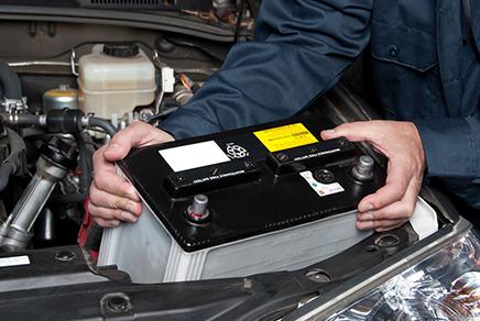 BP8DKT A car mechanic replaces a battery.